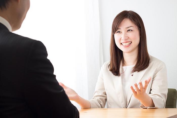スーツ姿で説明する女性と話を聞く男性